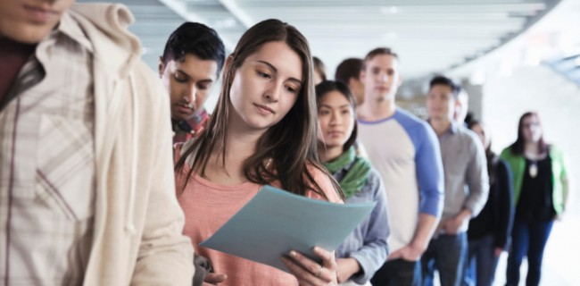 Large group of students standing in line at college campus