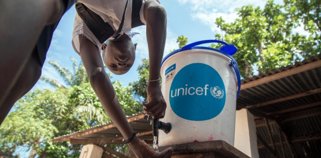 A girl washes her hands to help contain Ebola before entering a
